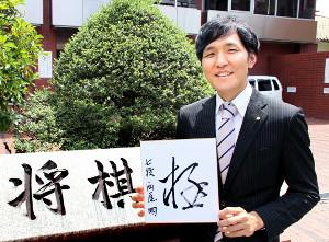 毎日の通勤先となる将棋会館前に立つ常務理事・西尾明七段。色紙に書いた言葉は「極(きわめる)」