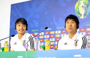 公式会見に臨む柴崎岳(左)と森保一監督(カメラ・宮崎 亮太)