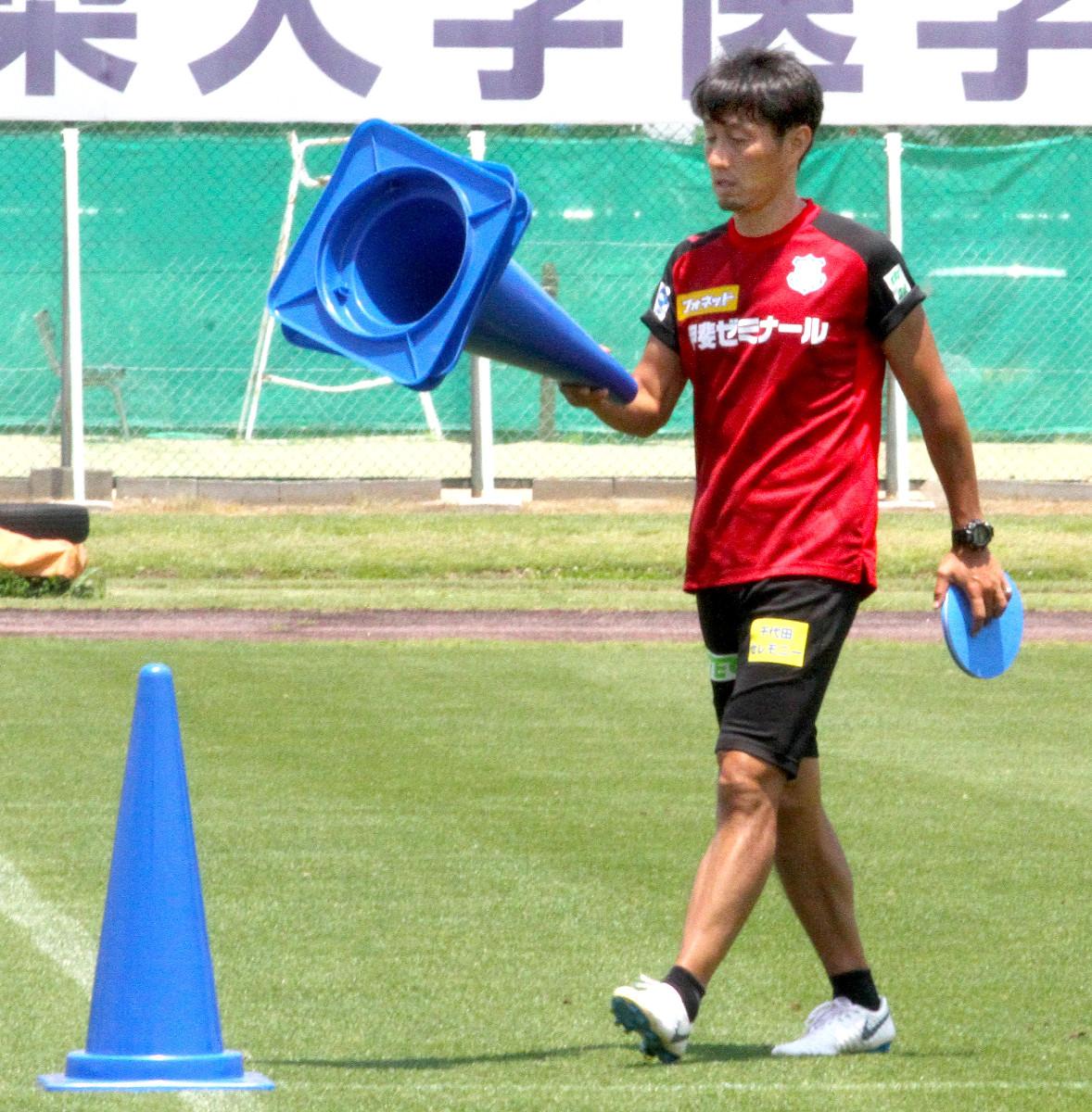 練習中にコーンを片づける甲府の伊藤彰監督