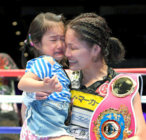 ベルトを肩に長女・実衣菜ちゃん(左)を抱き上げ涙する吉田(カメラ・竜田 卓)