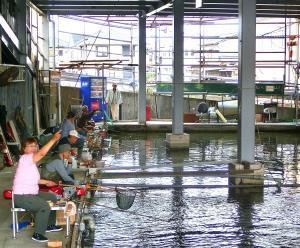 屋内釣り場で釣りをする峰松さん(手前)