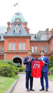 北海道庁を訪問し、鈴木道知事に限定ユニホームを贈呈した田中賢(左)