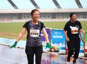 雨の中、笑顔でゴールする福本愛菜(左)