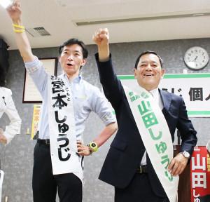 比例代表候補の宮本周司氏(左)との「Wしゅうじ」で拳を突き上げる山田修辞氏