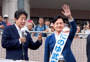 安倍首相(左)の応援を受け、手を振る自民党現職の二之湯氏