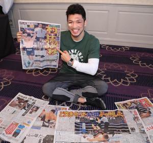 勝利を伝えるスポーツ報知を指さす村田諒太