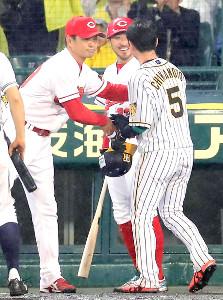 サイクル安打を記録した阪神・近本(右)をベンチで迎える全セ・緒方監督(左)