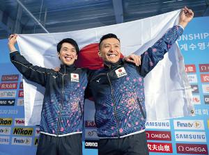 東京五輪が内定した寺内(右)と坂井は、日の丸を掲げ笑顔を見せた(カメラ・竜田 卓)