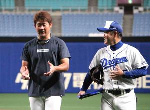 塚本コンディショニングコーチと談笑しながら練習を引き揚げる松坂(左)