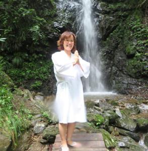 滝行衣を着て「龍神の滝」の前で笑顔