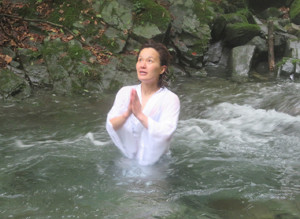 滝に打たれた後、川の中で手を合わせる