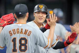 4回1死一塁、右越えに先制の2点本塁打を放った岡本和真は先発の菅野智之(18番)に迎えられ、声をかけられる(カメラ・泉 貫太)