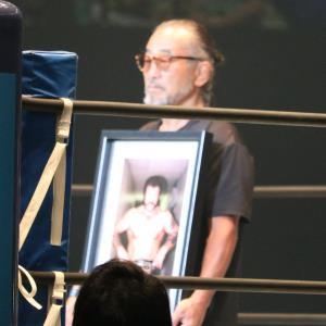 ハーリー・レイスさんの遺影を持ってリング中央に立ったタイガー服部レフェリー。名レスラーの追悼セレモニーが行われた