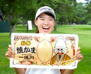 関係者から「タラタラしてんじゃね~よ」と同じ、よっちゃん食品工業が発売するお札を模したビッグサイズの駄菓子を贈られ笑顔を見せる渋野日向子(カメラ・竜田 卓)