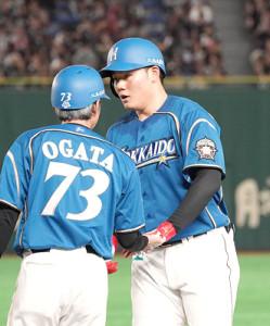 左前打で出塁した清宮(右)は緒方コーチとタッチする