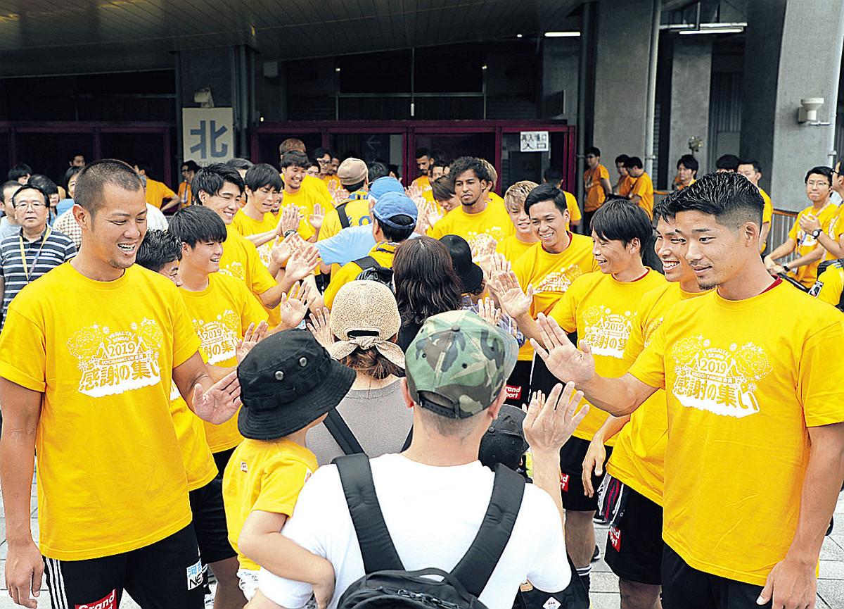 サポーターをハイタッチで出迎える仙台の選手たち