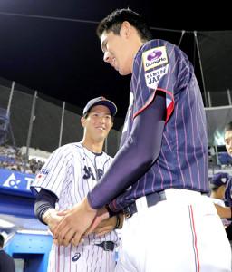 試合後、佐々木(右)と握手する明大・森下暢