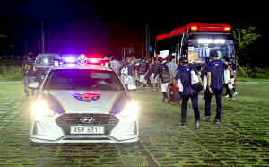 韓国の警察パトカーに警備されながらバスに乗り込むU18日本代表の選手たち