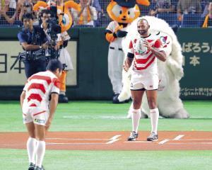 巨人―広島戦前、ラグビーボールで始球式をした田中(手前)とリーチ(カメラ・森田 俊弥)