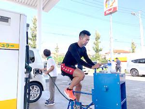 足こぎ式の給油機を使って給油作業を手助けする競輪のトップレーサー山賀雅仁