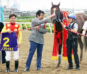 ノブワイルドをなでるTUBEの前田亘輝(左から2人目、左は左海誠)