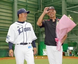 引退するロッテ・福浦和也内野手兼2軍打撃コーチに花束を贈呈した西武・松井稼頭央2軍監督(左)