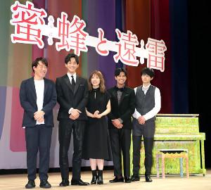 劇中にも登場するピアノをバックに完成披露イベントで挨拶する(左から)石川慶監督、松坂桃李、松岡茉優、森崎ウィン、鈴鹿央士