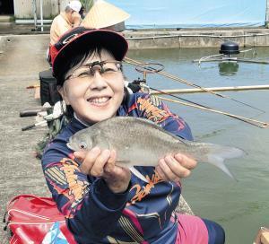 良型のヘラブナを手に笑顔の峰松さん