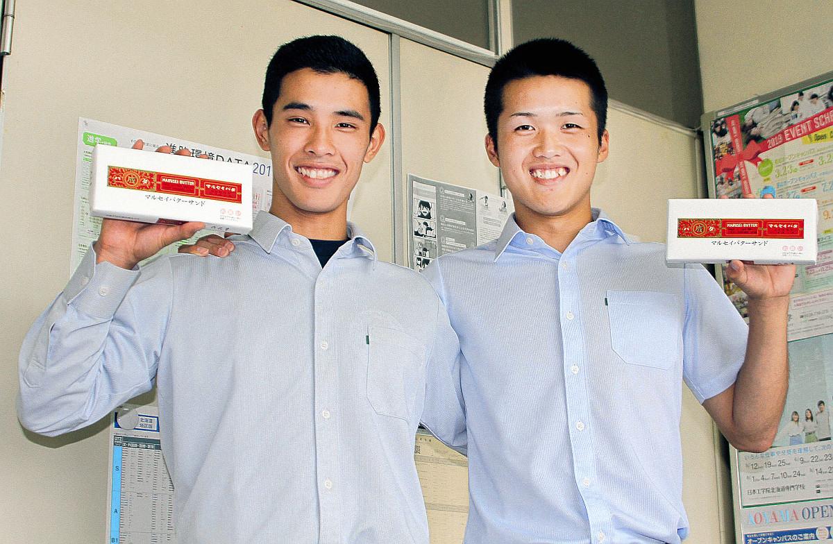 六花亭名物のマルセイバターサンドを手に笑顔を見せる北照・桃枝(右)と伊藤