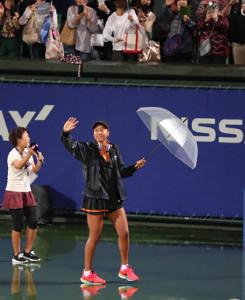 雨の中、再開を待つ観客の為にコートに出てきて手を振る大坂なおみ