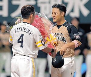 試合後、ソフトバンク・川島(左)から花束を受け取る日本ハム・田中賢