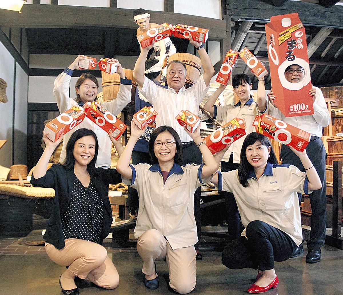 「白鶴 まる」を手に「まるポーズ」を決める白鶴酒造の社員たち
