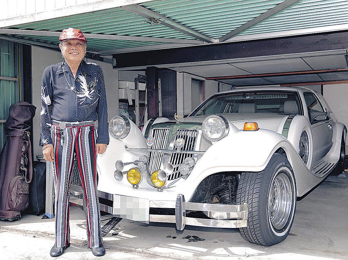 自慢の愛車をバックに自宅前に立つ佐藤忠志さん(2018年7月、一部加工)