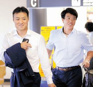 伊丹空港を出発する日本ハム田中賢(左)と鶴岡