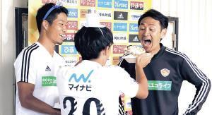 渡辺監督(右)の口にケーキを運ぶMF田中(左はDF常田)