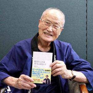 著書を手に笑顔を見せる松倉会長