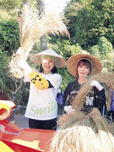 脱穀前の米を持って笑顔の小林幸子(左)と中川翔子