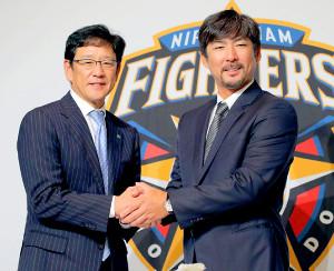 就任会見を行い、栗山監督(左)と握手する小笠原ヘッド兼打撃コーチ