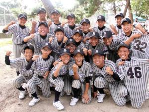 大阪狭山ナインは、この日欠場した選手のユニホームを掲げガッツポーズ