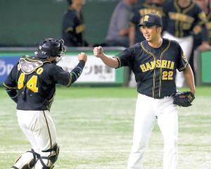 8回から登板し、2イニングを無失点に抑えた藤川(右)は捕手・梅野と勝利のグータッチを交わす