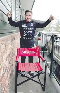 報道陣から名前入りの椅子を受け取り、笑顔を見せる札幌のペトロヴィッチ監督
