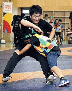 イベントで小学生のタックルを受ける乙黒拓(左)