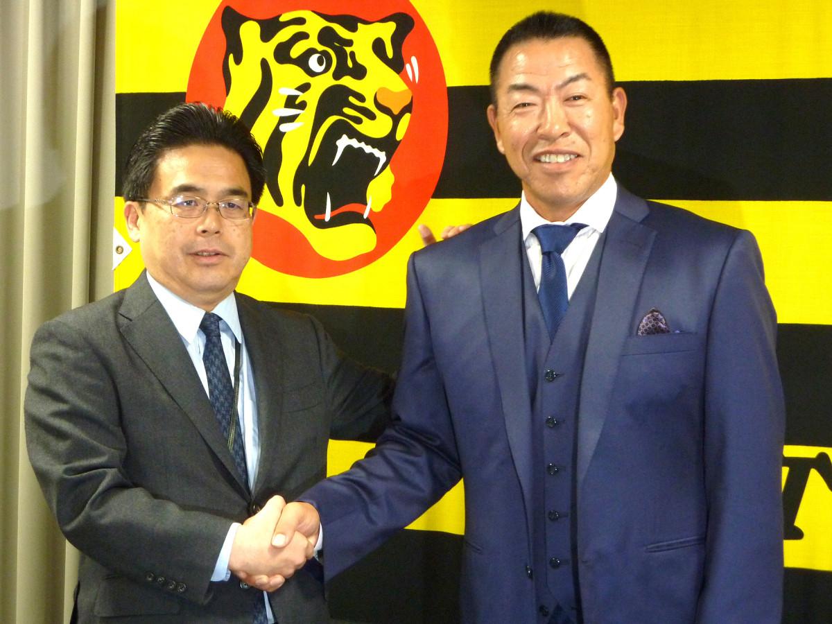 就任会見で谷本球団本部長(左)と握手する阪神・井上打撃コーチ
