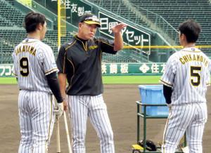 高山(左)と近本(右)に指導する新任の井上打撃コーチ