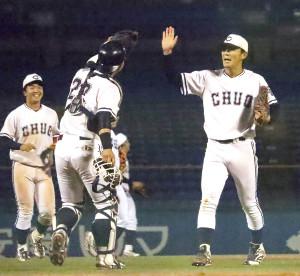 完全優勝を決め、ハイタッチする(右から)皆川喬涼投手と古賀悠斗捕手
