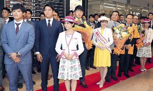 宮崎空港に到着し、歓迎セレモニーで花束を手にする(2列目左から)石川、桜井、岡本、原監督らナイン(カメラ・関口 俊明)
