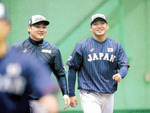 侍ジャパンの練習中、笑顔でウォーミングアップする丸佳浩(左)と鈴木誠也