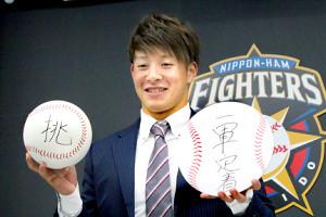 契約更改を終え、笑顔で写真撮影に応じる吉田輝