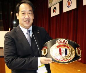 日本連盟の内田会長は今年の全日本選手権から優勝者に授与するベルトを手に笑顔