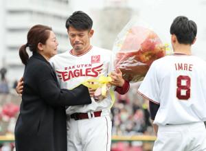 幸子夫人(左)から花束を受け取り、涙を流す今江(右は息子の陸斗くん)